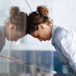 woman-banging-her-head-against-a-wall-outside-office_bkt_14860